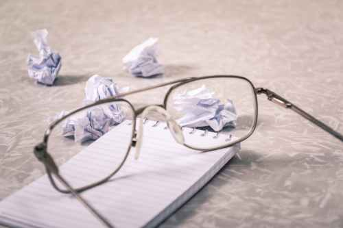 close up photography of eyeglasses near crumpled papers